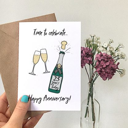 champagne 25th anniversary card in hand